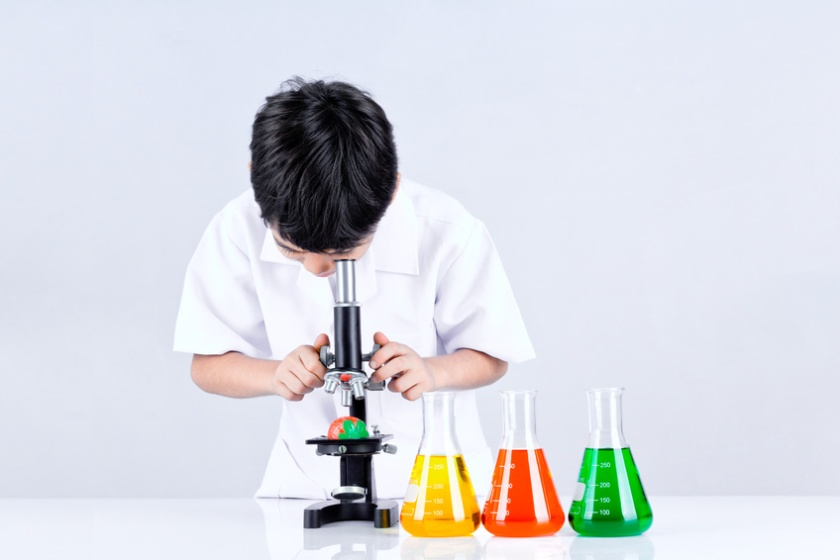 Asian boy conduct an experiment microscope